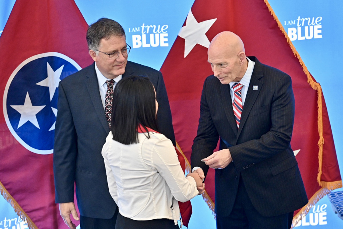 MTSU ROTC cadet Neily Jiminez, center, received a Challenge Coin, which is a tradition in military history, from retired U.S. Army Lt. Gen. Keith M. Huber, right, and MTSU Provost Mark Byrnes watches Wednesday, Dec. 4, during the 15th Graduating Veterans Stole Ceremony at the Miller Education Center on Bell Street. Student veterans received their red stoles that can be worn Saturday, Dec. 14, during MTSU commencement ceremonies. Huber is senior adviser for veterans and leadership initiatives at MTSU. (MTSU photo by J. Intintoli)