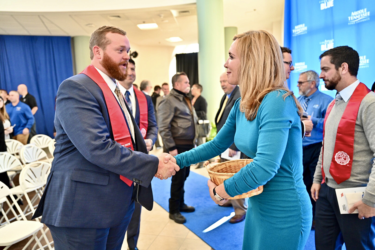 MTSU senior Hal Robertson, left, received congratulations and a commemorative alumni coin from Hilary Miller, director of the MTSU Charlie and Hazel Daniels Veterans and Military Family Center, Wednesday, Dec. 4, following the conclusion of the 15th Graduating Veterans Stole Ceremony in the Miller Education Center on Bell Street. Nearly 25 student veterans were recognized during the event. (MTSU photo by J. Intintoli)