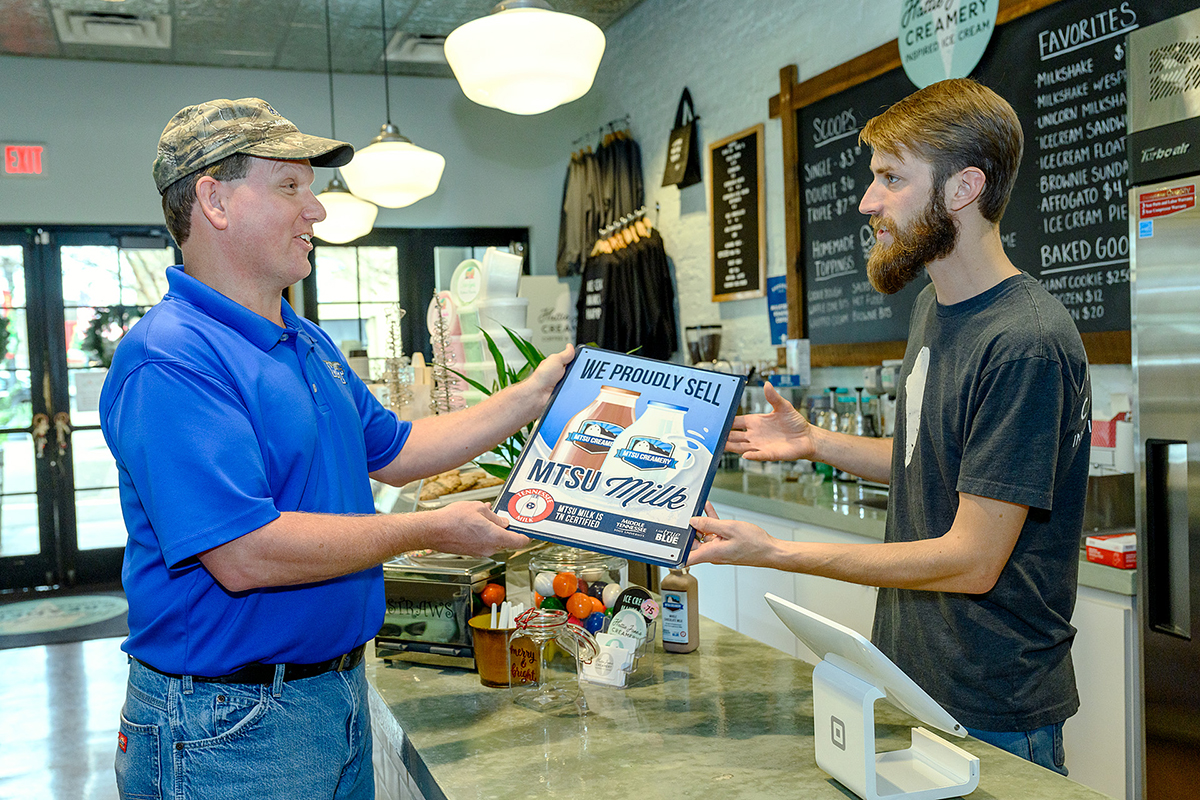 MTSU Creamery Manager Steve Dixon, left, presented a tin sign promoting MTSU milk to Jacob Hendley, ice cream ambassador and coffee barista at Hattie Jane's Creamery in downtown Murfreesboro, one of 15 area businesses buying milk from the university. The signs are helping to promote MTSU milk as a 100 percent-certified Tennessee Milk product. (MTSU photo by J. Intintoli)