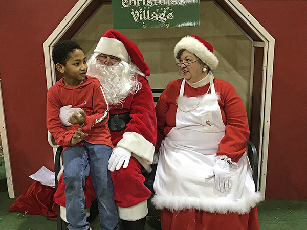 Eric Weatherly, 7, of La Vergne, Tenn., spent time with Santa and Mrs. Claus (aka Tom and Debbie Strobel) at the MTSU Agritourism Club's recent Winter Village in the Tennessee Livestock Center on Greenland Drive. Weatherly is the son of Stacy and Jessie Weatherly. Jessie Weatherly is a specialist in the MTSU chemistry lab. (MTSU photo by Randy Weiler)
