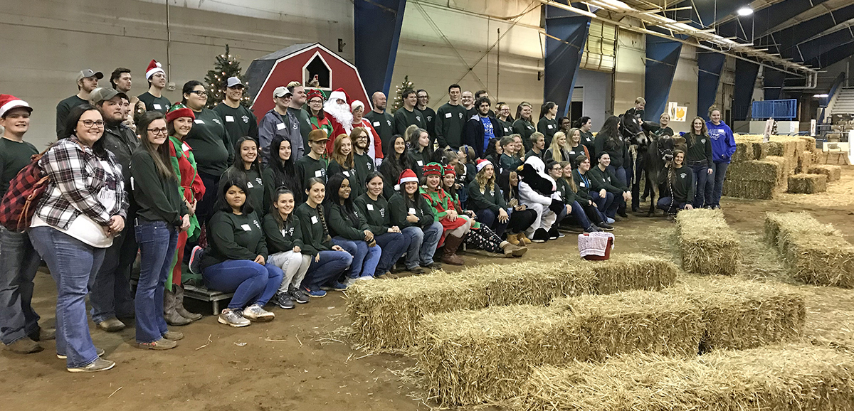 Volunteers for the Dec. 7 Winter Village held in the Tennessee Livestock Center on Greenland Drive gathered following the event for a group photo. (MTSU photo by Randy Weiler)