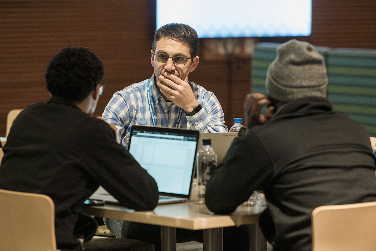 In this file photo, MTSU Data Science Institute director Charlie Apigian, center, consults with competitors at the fourth annual MTSU Hackathon (HackMT), where students, alum, faculty, and industry mentors from MTSU (as well as from other universities across the state) spend 36 straight hours developing computer software technology products, and then present them to be judged at a fair in the Science Building Atrium. (MTSU file photo)
