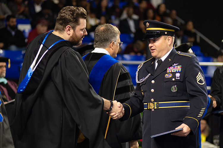 New MTSU aerospace graduate James D. Summers of Woodbury, Tennessee, center, accepts congratulations from country music entertainer, former MTSU student and guest speaker Chris Young during the Class of 2019's morning commencement ceremony inside Murphy Center on Saturday, Dec. 14. (MTSU photo by James Cessna)
