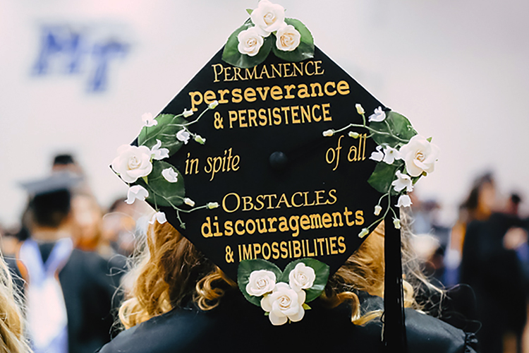 An MTSU Class of 2019 graduate proudly displays her customized mortarboard, complete with an inspirational quote from Scottish historian and essayist Thomas Carlyle, while preparing for the university's fall 2019 commencement ceremonies inside Murphy Center on Saturday, Dec. 14.(MTSU photo by GradImages)