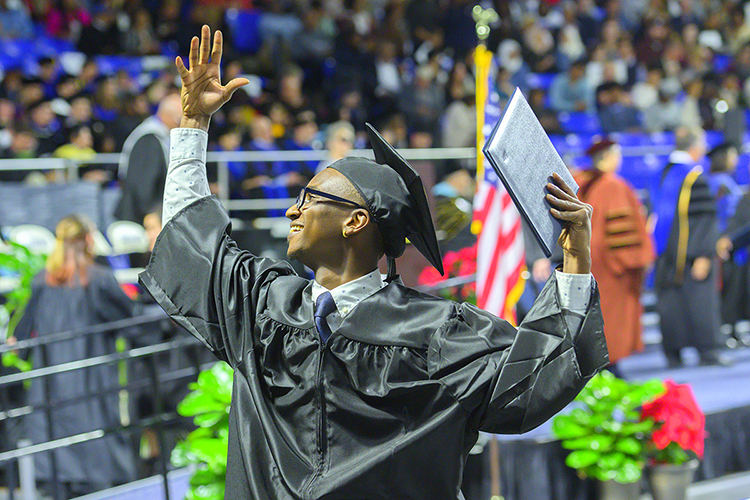 A new MTSU graduate, degree in hand, waves to family and friends inside Murphy Center Saturday, Dec. 14 at the university's fall 2019 afternoon commencement ceremony. (MTSU photo by Cat Curtis Murphy)