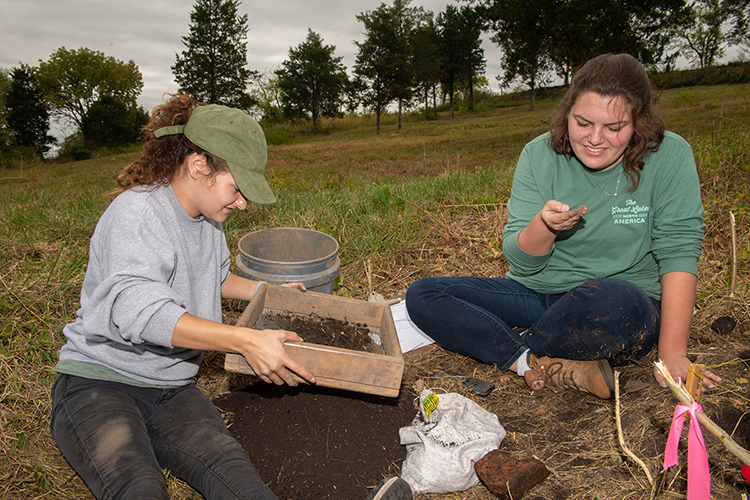 Anna Yuhas, a sophomore forensic science major from Saulsbury, Tennessee, and Madeleine Laderoute, a graduate teaching assistant, sift through dirt for artifacts on the Bass Street Community Archaeology Project at Fort Negley in Nashville. (MTSU photo by James Cessna)