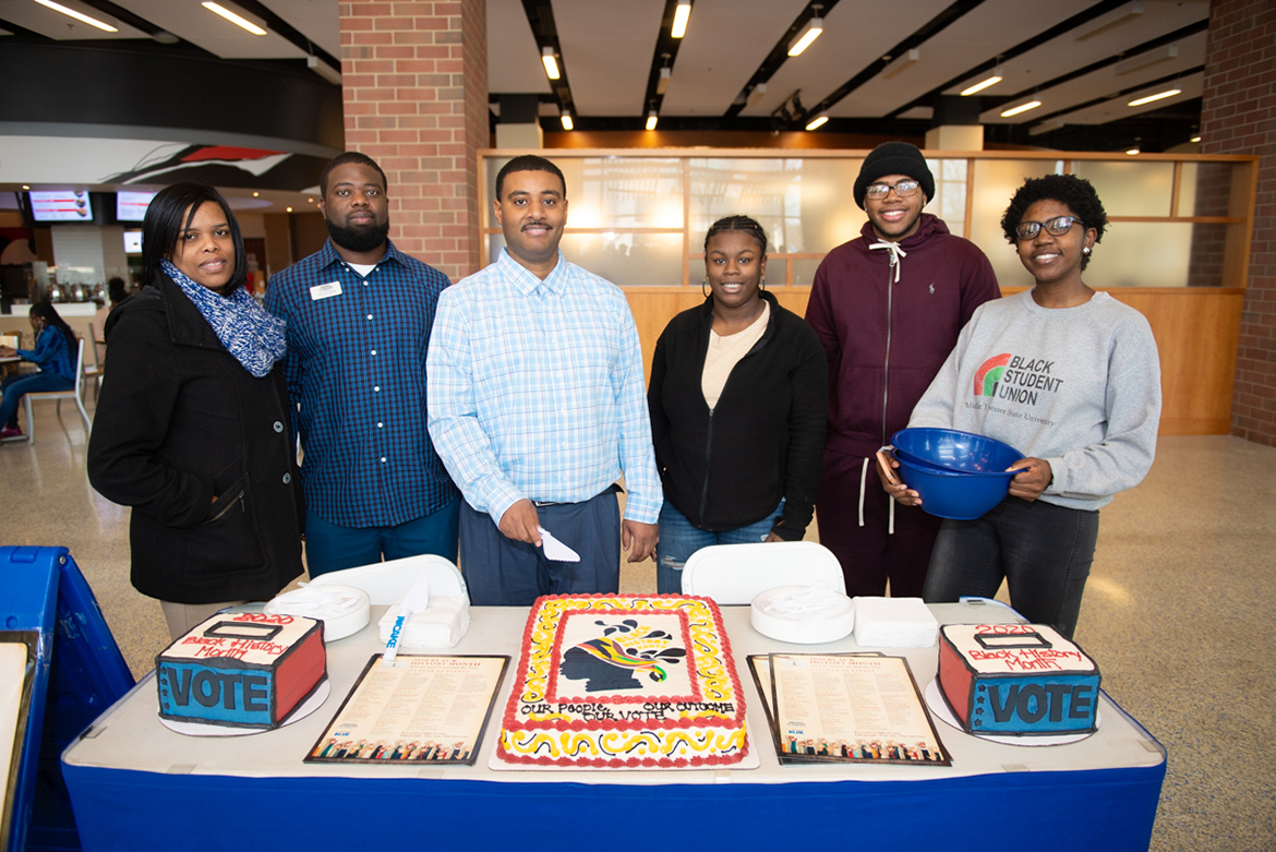 Some members of the 2020 MTSU Black History Month Committee prepare to cut the celebratory cake at the Feb. 3 kickoff event held in the Student Union atrium. Pictured, from left, are Danielle Rochelle, Chris Rochelle, Daniel Green, Daisha Green, Lamont Lockridge and Ashley Lowe. (MTSU photo by James Cessna)