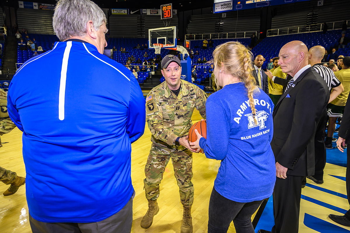 An instructor from The Sabaulaski Air Assault School, 101st Airborne Division (Air Assault), second from left, delivers the MTSU-Marshall game ball in Murphy Center to an MTSU ROTC student in January 2019 as athletics director Chris Massaro, left, and Keith M. Huber, a retired lieutenant general with a 38-year military career and MTSU's senior adviser for veterans and leadership initiatives, observe. Members of the 101st return Thursday, Jan. 30, with a featured rappelling demonstration by the Screaming Eagle soldiers before the MTSU Lady Raiders game against UTEP in Murphy Center during Blue Raider Veteran and Military Appreciation Night. The soldiers learn the craft at The Sabalauski Air Assault School at Fort Campbell. (MTSU file photo by Eric Sutton)