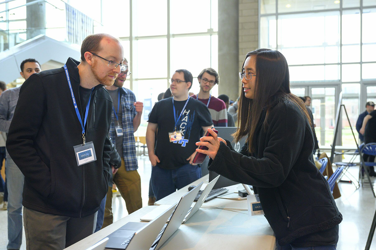 MTSU computer science assistant professor Josh Phillips, left, listens as Jessica Wijaya, a junior computer science major, explains her team's project during the science fair portion of the fifth annual HackMT at MTSU, which concluded Sunday, Jan. 26, in the Science Building's Liz and Creighton Rhea Atrium. (MTSU photo by Cat Curtis Murphy)