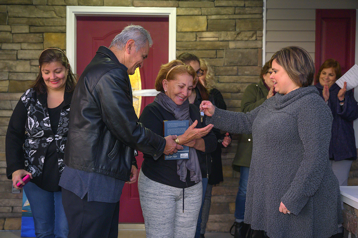 MTSU's Jackie Victory, right, director of MTSU Student Organizations and Service, hands the keys to the new home for Carlos Rivero-Odermatt and Rafela Aldas Wednesday, Jan. 8, on East Castle Street, as their daughter, Annely Rivero Quinones, left, smiles with approval. MTSU students and other volunteers helped build the home. (MTSU photo by Cat Curtis Murphy)