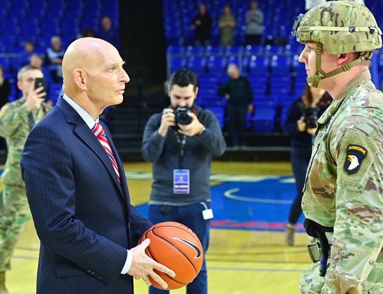 Retired Army Lt. Gen. Keith Huber, left, accepts the game ball from a member of the U.S. Army's 101st Airborne Division after it was rappelled from the rafters onto the Hale Arena hardwood Jan. 30 as part of MTSU Women's Basketball's veteran appreciation night at Murphy Center. Huber, senior advisor for veterans and leadership initiatives at MTSU, spent nine years of his 38-year military career with the 101st. (MTSU photo by Cat Curtis Murphy)