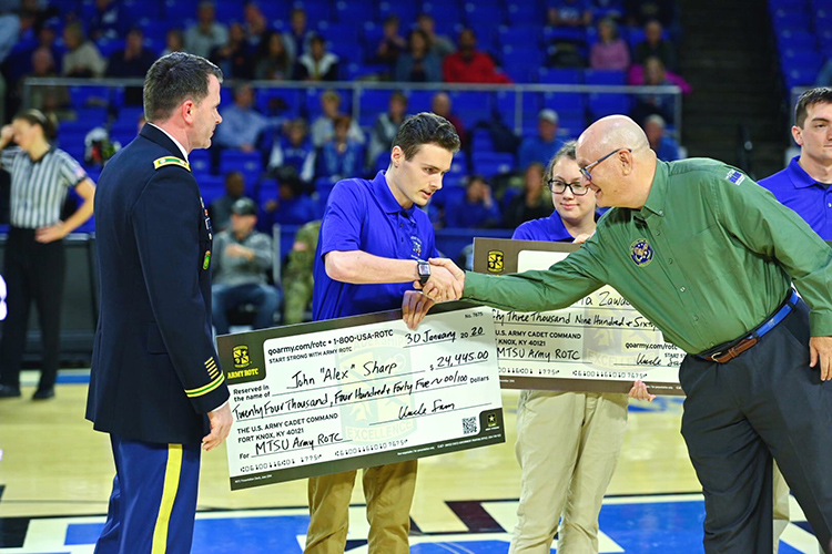 Andrew Oppmann, right, MTSU vice president for marketing and communications and Army Reserve ambassador, congratulates sophomore ROTC cadet John Sharp after the student received a Army Reserve scholarship during a special presentation Jan. 30 at the MTSU Women's Basketball's veteran appreciation night at Murphy Center. At far left is Army by Lt. Col. Carrick McCarthy, MTSU's professor of military science and head of the Blue Raider Battalion. (MTSU photo by Cat Curtis Murphy)