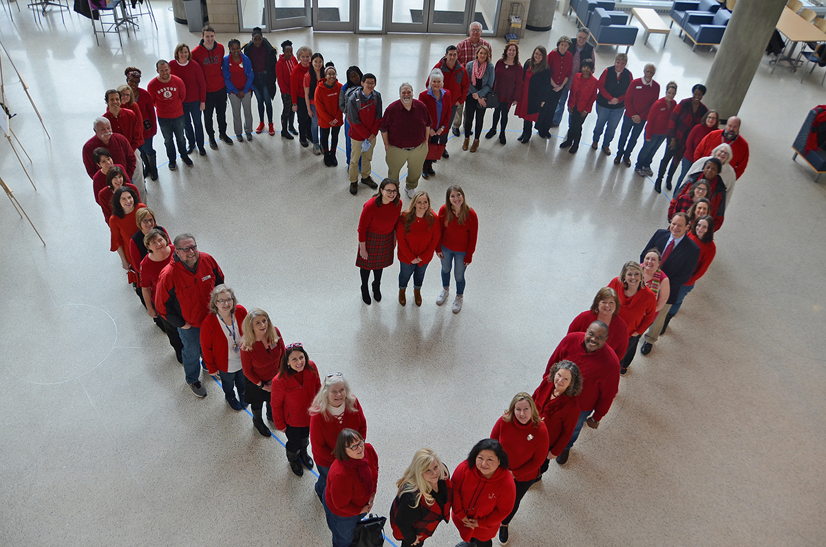 "With nearly everyone wearing red on ""Wear Red Day,"" MTSU staff and students form a large human heart in the Science Building's Liz and Creighton Rhea Atrium Feb. 7 as they learned about risks and symptoms of heart disease in women and men. This year's honorees Trisha Murphy, left, Emily Hasty and Hannah Daigle stand in the center area. (MTSU photo by Randy Weiler)"