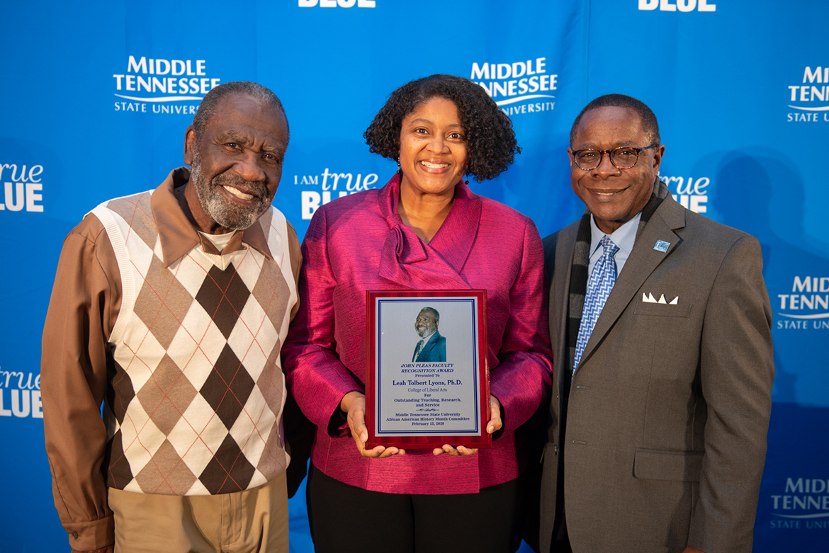 Leah Tolbert Lyons, center, an associate professor of French and interim associate dean of the College of Liberal Arts, accepts the 2020 John Pleas Faculty Award at a Feb. 13 ceremony in the Sam H. Ingram Building. At left is John Pleas, professor emeritus of psychology, for whom the award is named. At right is MTSU President Sidney A. McPhee. (MTSU photo by James Cessna)