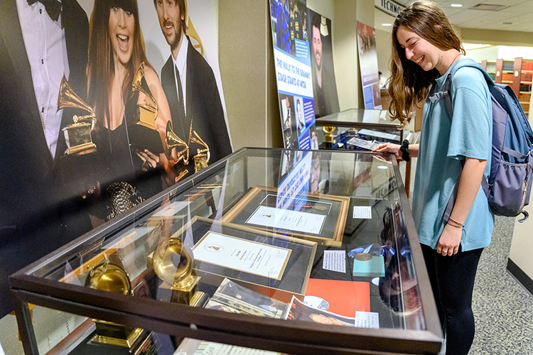 "MTSU freshman global studies major Maggie Dennis of Christiana, Tenn., learns more about the MTSU students, alumni and faculty connections to the Grammy Awards while inspecting a display case in an exhibit at the university's James E. Walker Library, ""A Legacy of Excellence: MTSU at the Grammys."" The exhibit is on display through February. (MTSU photo by J. Intintoli)"