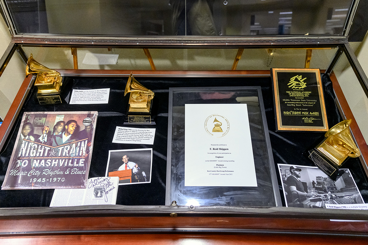 "Some of the Grammy recognition for MTSU alumni is shown inside a display case in ""A Legacy of Excellence: MTSU at the Grammys,"" an exhibit at the university's James E. Walker Library on view through the end of February. The items include, clockwise from top left, a Grammy won by MTSU recording industry lecturer and Master of Arts in Liberal Arts alumnus Roy E. ""Bubba"" Smith, producer of the 2000 best traditional soul album, ""You Can Make It"" by Shirley Caesar; the Grammy that alumnus Michael Gray (B.S. '92, M.S. '97) received as co-producer of the 2005 best historical album, ""Night Train to Nashville: Music City Rhythm & Blues, 1945–1970""; a certificate of recognition for 1994 alumnus F. Reid Shippen, who engineered the 2012 best country duo/group performance Grammy winner, ""Pontoon,"" by Little Big Town; a plaque from the Recording Academy, then the National Academy of Recording Arts and Sciences, recognizing MTSU in the inaugural NARAS Student Music Awards for outstanding achievement in the jazz/big band category; Shippen's Grammy for engineering the 2007 best pop/contemporary gospel album, ""Wherever You Are"" by Third Day, and a photo of him in the studio; and a photo of Gray alongside a copy of the ""Night Train to Nashville"" album and its liner notes autographed by music legend Etta James. (MTSU photo by J. Intintoli)"