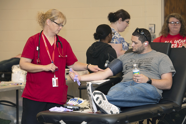 "MTSU senior aerospace major Kyle Dion watches an American Red Cross phlebotomist point out a good strong vein for him to donate blood at the university's September 2019 ""Battle of the Branches"" blood drive. MTSU is sponsoring its 2020 valentine blood drive on Monday, Feb. 10, from 10 a.m. to 4 p.m. in Room 322 of the Keathley University Center. (MTSU file photo by James Cessna)"