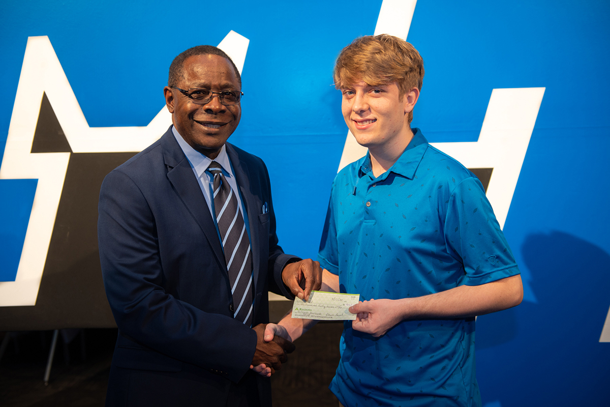 MTSU President Sidney A. McPhee, left, receives a check for $740 from Nathan Lathrop of Chattanooga, Tenn., Monday, Feb. 17, as a donation to the Raider Relief fund to assist with Hurricane Dorian disaster efforts in the Bahamas, McPhee's native country, in the Student Union Ballroom. Lathrop and four friends who are Center for Creative Arts classmates held a yard sale to raise the money. Lathrop, who plans to start at MTSU in August, attended the MTSU Celebration of Scholars event. (MTSU photo by James Cessna)