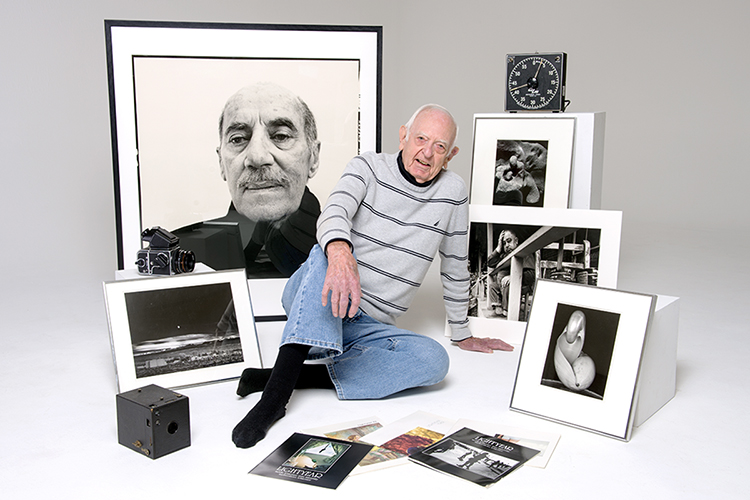 MTSU Professor Emeritus Harold L. Baldwin poses with prints by internationally recognized photographic masters from the university's million-dollar-plus collection, along with copies of the MTSU photography magazine Lightyear, vintage cameras and a darkroom timer in this 2012 file photo. Baldwin, 93, founder of both MTSU's photography program and the renowned campus photo gallery that bears his name, died March 19. (MTSU file photo by J. Intintoli)
