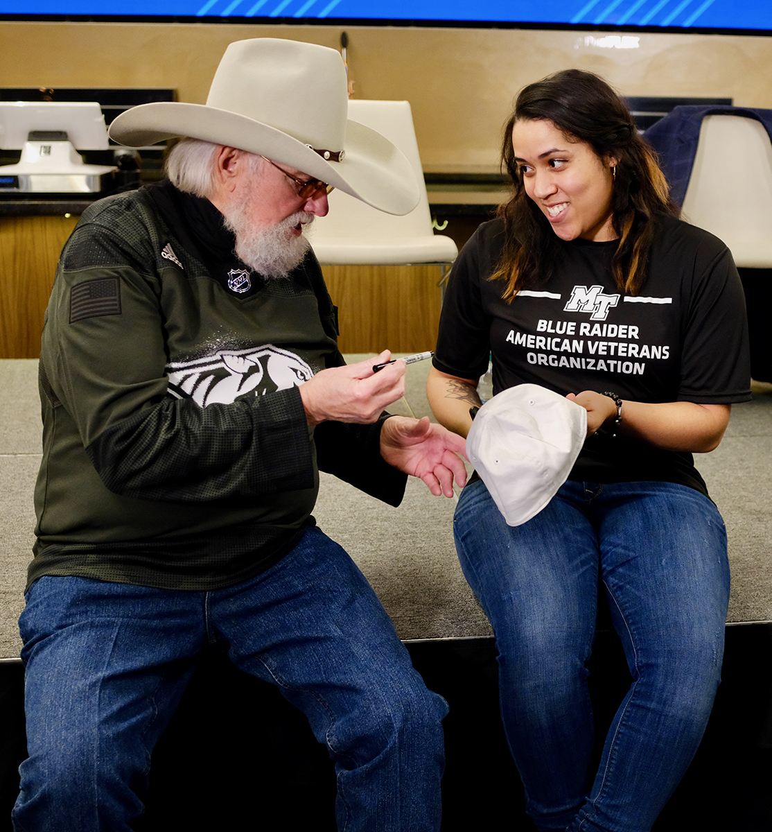 Country Music legend and MTSU Charlie and Hazel Daniels financial supporter Charlie Daniels signs an autograph for MTSU student veteran Teresa Carter, 2019-20 president of the Blue Raider American Veterans Organization, or BRAVO, Monday, March 2, during the MTSU-Nashville Predators announcement at Bridgestone Arena. (MTSU photo by David Foster)
