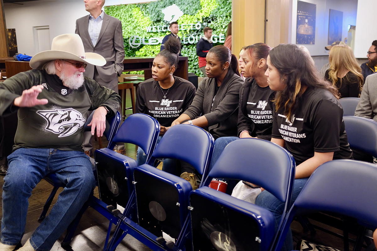 Country Music Hall of Fame member Charlie Daniels, left, visits with MTSU student veterans Tatyana Braswell, Sheneca Burnett, Kwantisha Farmer and Teresa Carter while awaiting the announcement of the partnership extension between the Nashville Predators and MTSU Monday, March 2, in the Lexus Lounger area at Bridgestone Arena, home of the Preds. (MTSU photo by David Foster)