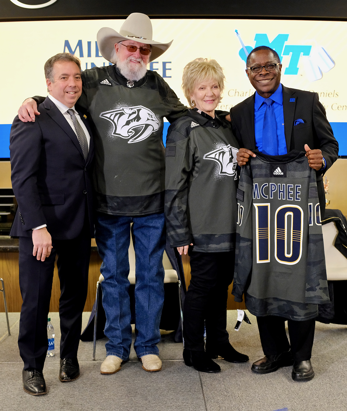 Nashville Predators President and CEO Sean Henry, left, legendary musician Charlie Daniels, Hazel Daniels and MTSU President Sidney A. McPhee are shown with special edition Predators' sweaters presented by the team Monday, March 2, at the Bridgeston Arena. The Predators announced the creation of the General's Fund during a news conference. (MTSU photo by David Foster)