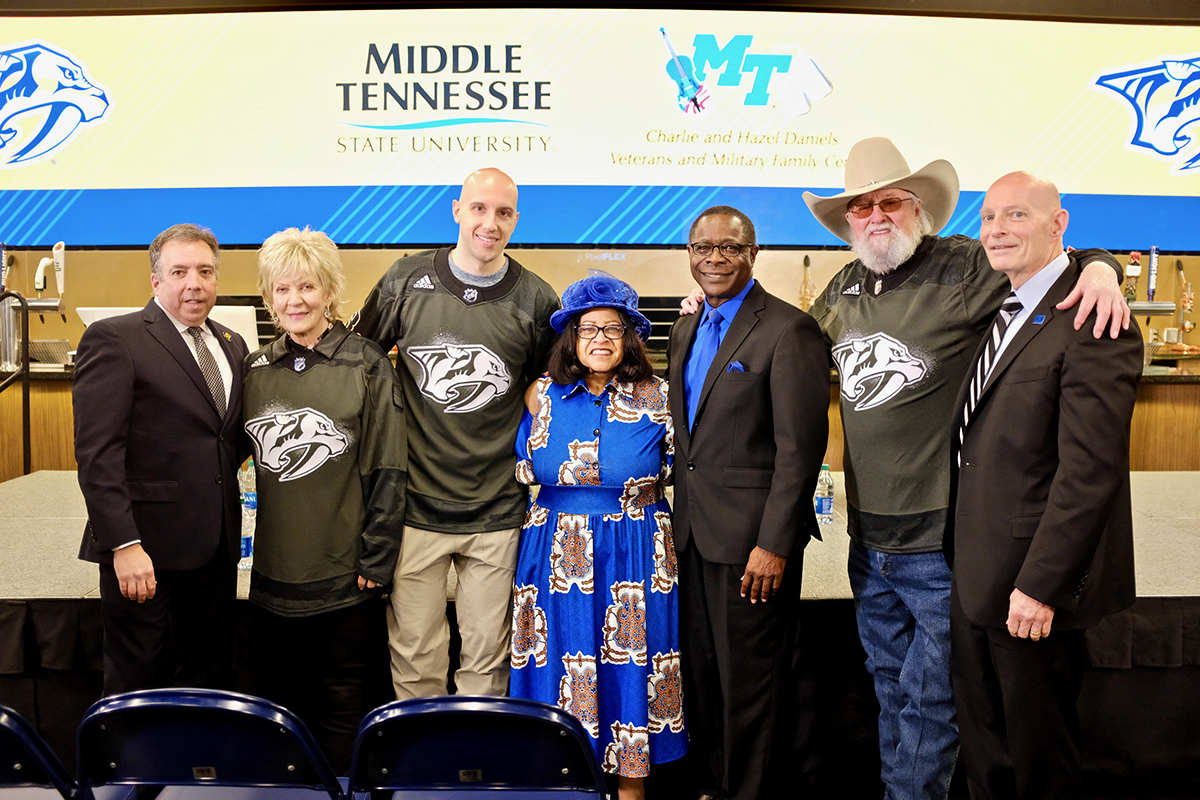 Predators President and CEO Sean Henry, left, Hazel Daniels, Preds center Nick Bonino, Elizabeth McPhee, MTSU President Sidney A. McPhee, Charlie Daniels and MTSU's Keith M. Huber celebrate the extended partnership between the university and NHL club Monday, March 2, at the Lexus Lounge area inside Bridgestone Arena. (MTSU photo by David Foster)