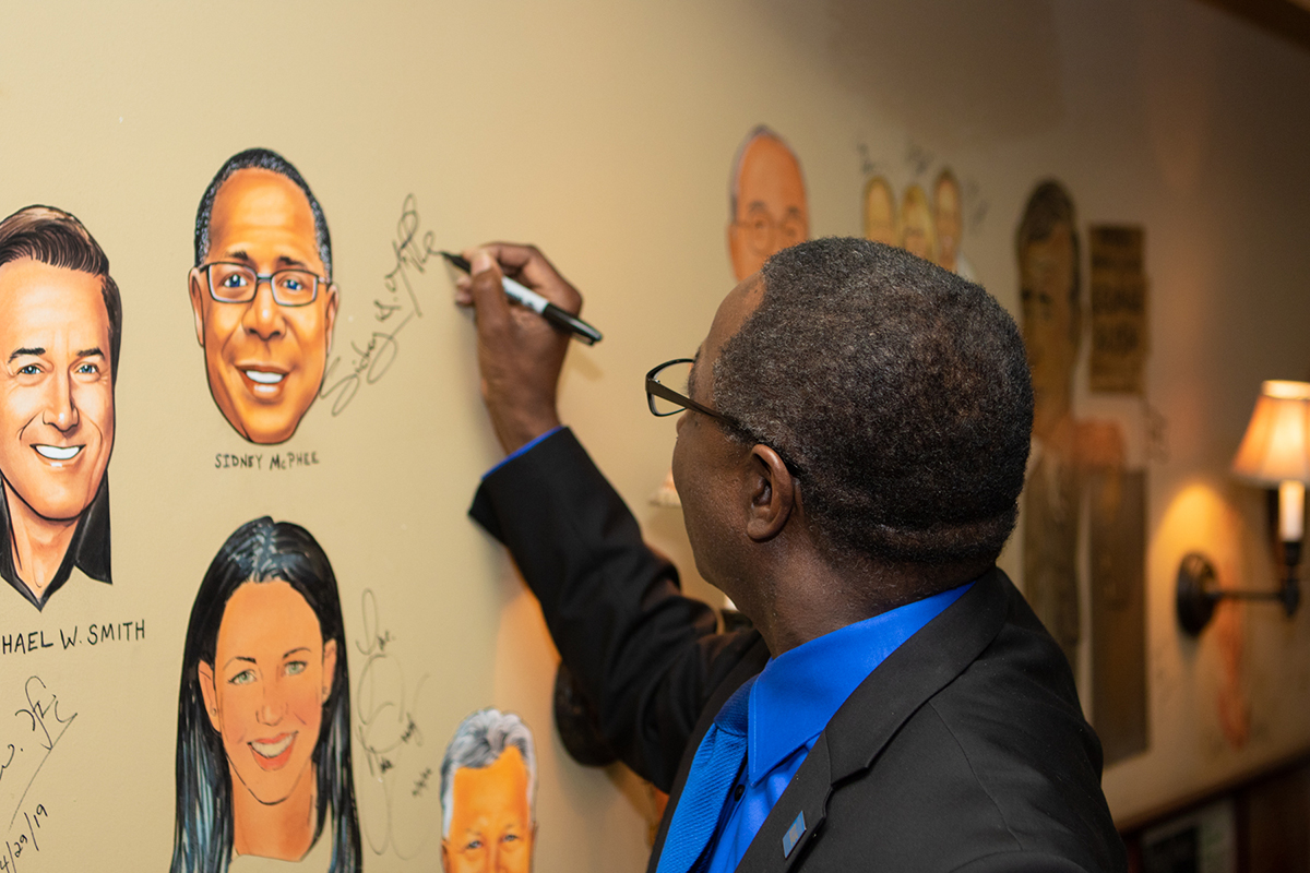MTSU President Sidney A. McPhee signs his name beside the caricature of himself that now is part of the walls at The Palm Nashville restaurant in downtown Nashville, Tenn. McPhee was surprised to learn that his likeness joins hundreds more at the fine dining establishment. He was in Nashville for the MTSU-Nashville Predators news conference to announce the extending of the partnership between the two organizations. (MTSU photo by James Cessna)