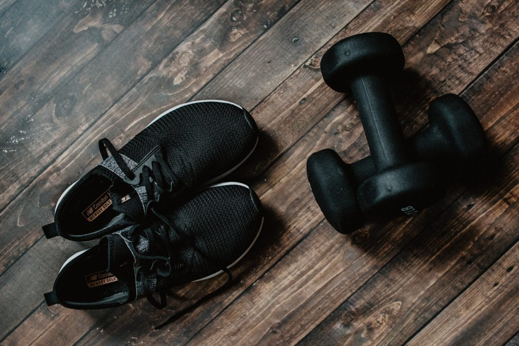 Tennis shoes and weights on a hardwood floor. Photo by Kelly Sikkema on Unsplash