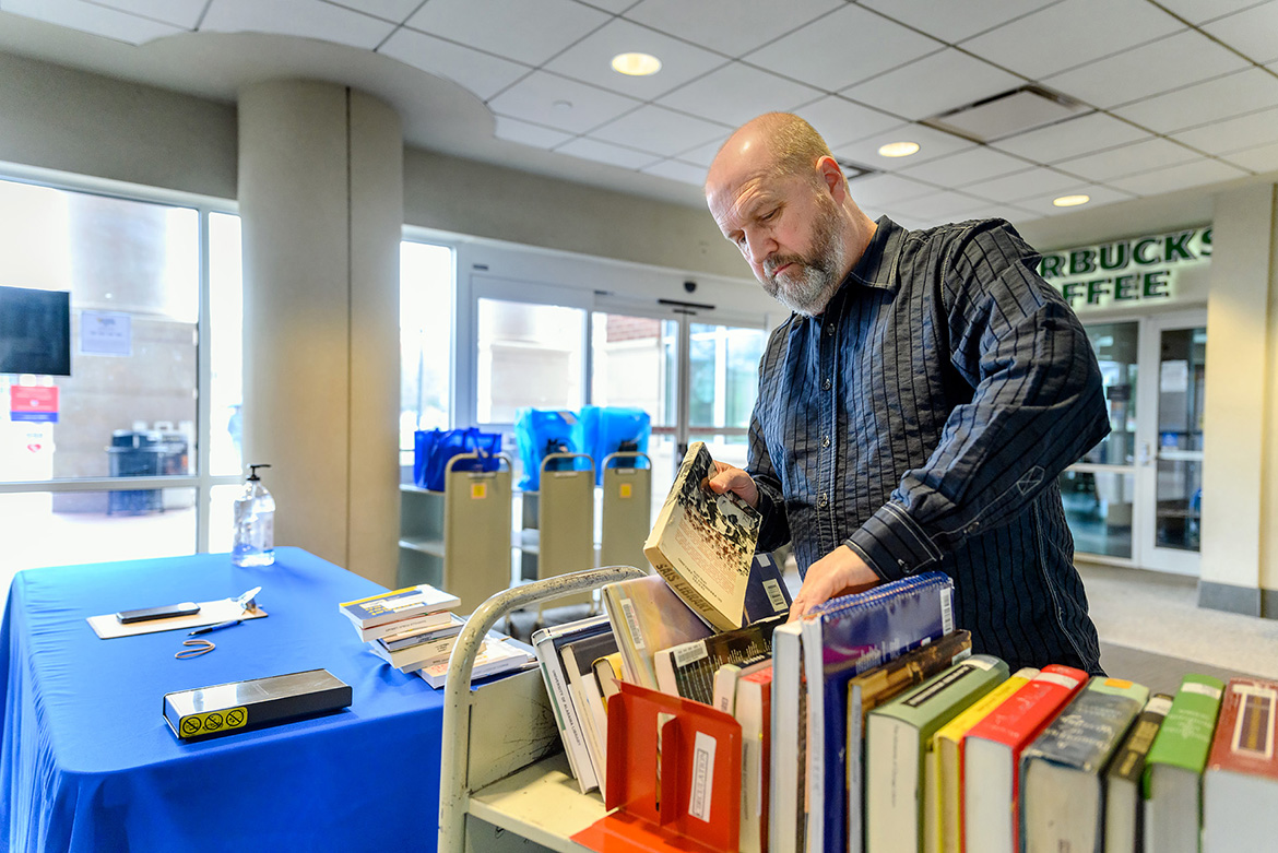 "Paul Burt, a circulation assistant in the James E. Walker Library, prepares books in the library vestibule to be checked out as part of the library's ""Pull and Hold"" service during the COVID-19 outbreak. (MTSU photo by J. Intintoli)"