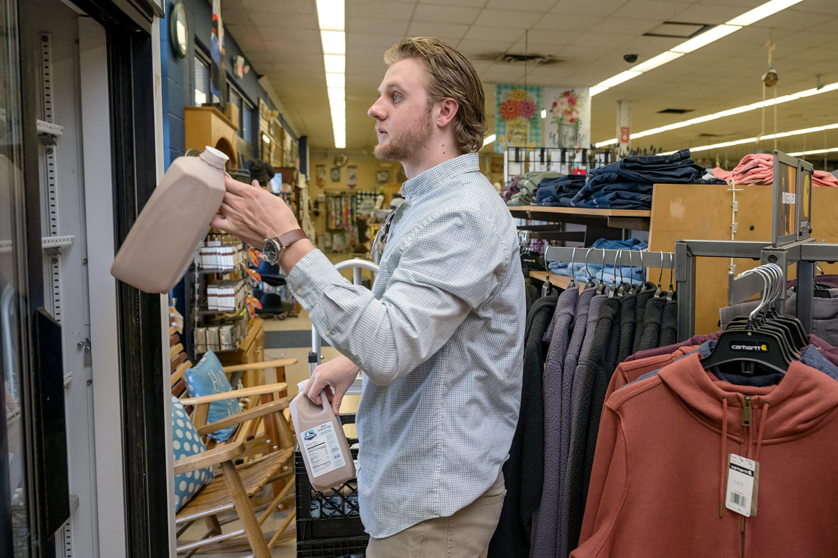MTSU senior agribusiness major Brendon Puckett of Gallatin, Tenn., stocks the cooler shelves with the milk he delivered to the Tennessee Farmers Co-Op on Middle Tennessee Boulevard Wednesday, March 25. (MTSU photo by J. Intintoli)