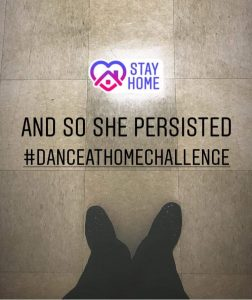 "Cassidy Johnson takes a picture of her feet in the dorm hallway, with text superimposed over the image saying ""And so she persisted, #dance at home challenge"""