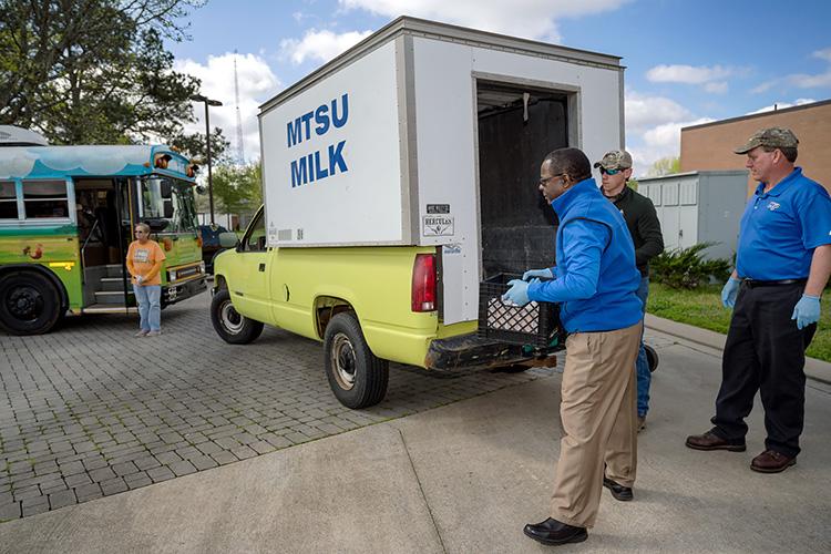 MTSU President Sidney A. McPhee, front, helps unload donated bottles of MTSU milk Wednesday, April 1, with MTSU Creamery manager Steve Dixon, right, and student worker Jacob Wade outside Hobgood Elementary on Baird Lane. The milk helped shore up a temporary shortage for the Murfreesboro City Schools' CHOW bus mobile meals program. (MTSU photo by J. Intintoli)
