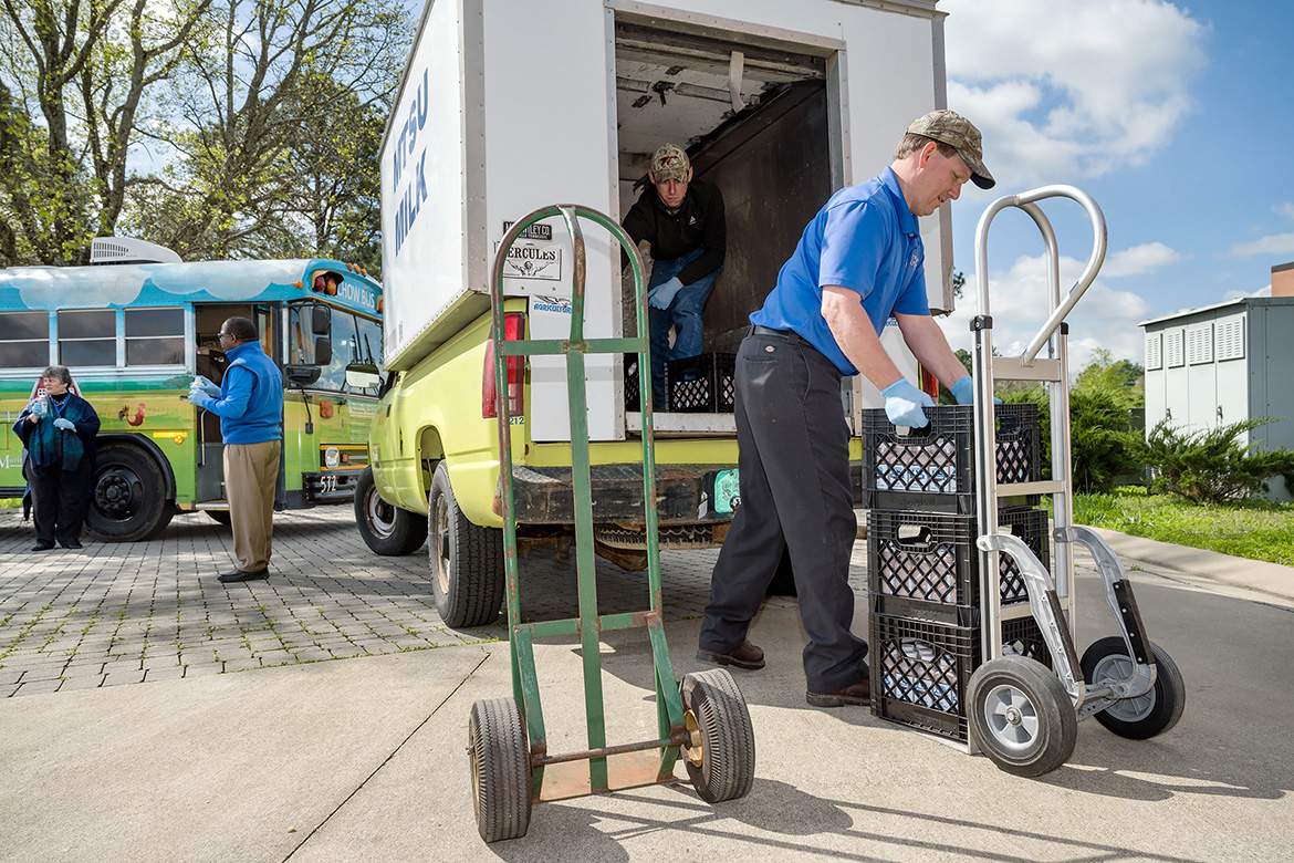 MTSU Creamery manager Steve Dixon, front, and student worker Jacob Wade unload donated bottles of MTSU milk Wednesday, April 1, outside Hobgood Elementary on Baird Lane for the Murfreesboro City Schools' CHOW bus mobile meals program. At left are MTSU President Sidney A. McPhee and Murfreesboro City Schools Director Linda Gilbert. (MTSU photo by J. Intintoli)