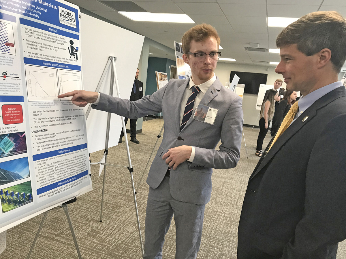 MTSU senior Aric Moilanen, left, a physics major from Crossville, Tenn., explains his quantum materials research to state Rep. Charlie Baum, an MTSU finance professor, in late February during the Posters at the Capitol event in Nashville, Tenn. Moilanen's research poster will be one of 150-plus at the virtual Scholars Week expo this week. (MTSU file photo by Randy Weiler)