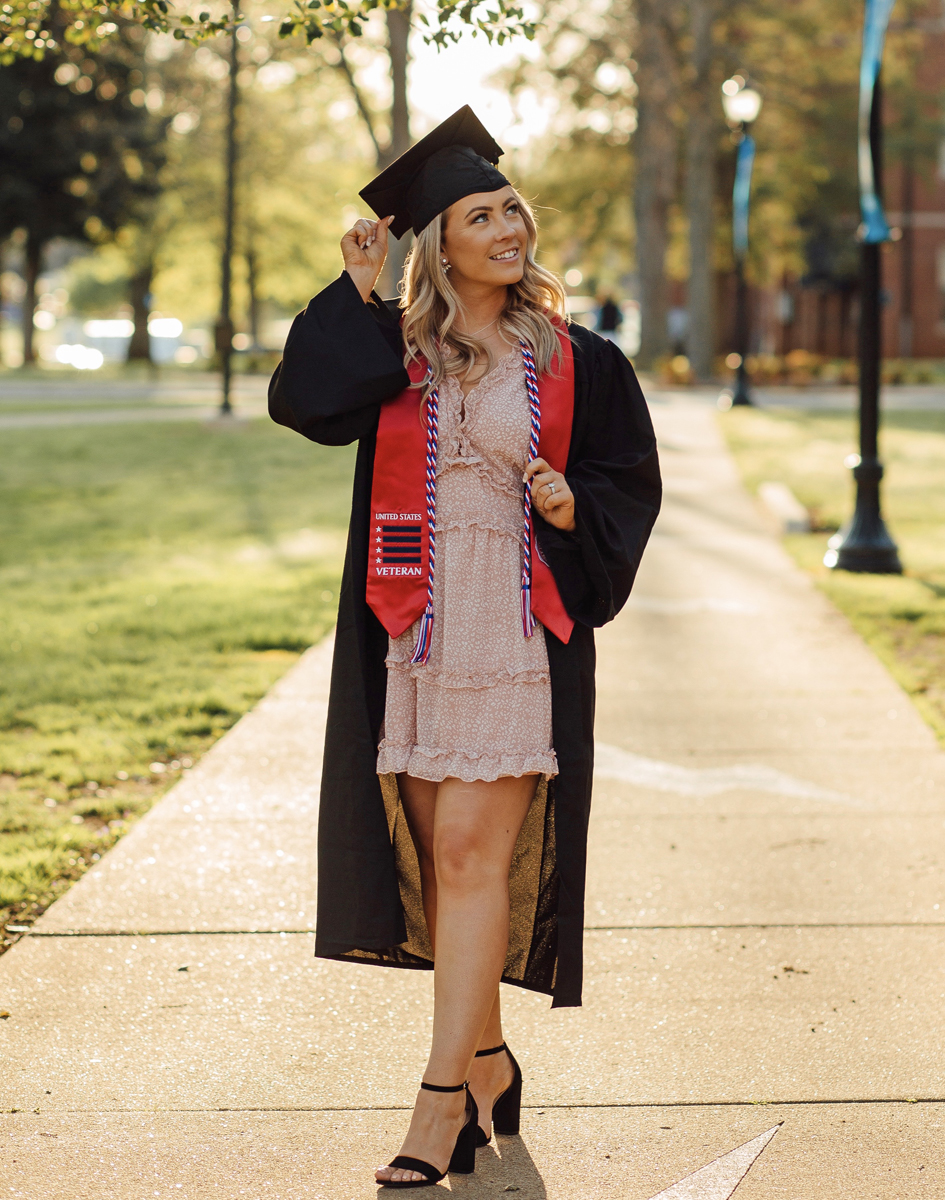 Wearing her MTSU red stole, graduating student veteran Vanessa VanCleve had professional cap-and-gown photos taken, only to learn the May 2020 MTSU commencement was canceled because of the coronavirus pandemic. She has been in the School of Concrete and Construction Management program since 2017. (Photo by Lindsay Collett/SincerelyLindsayPhotography.com)