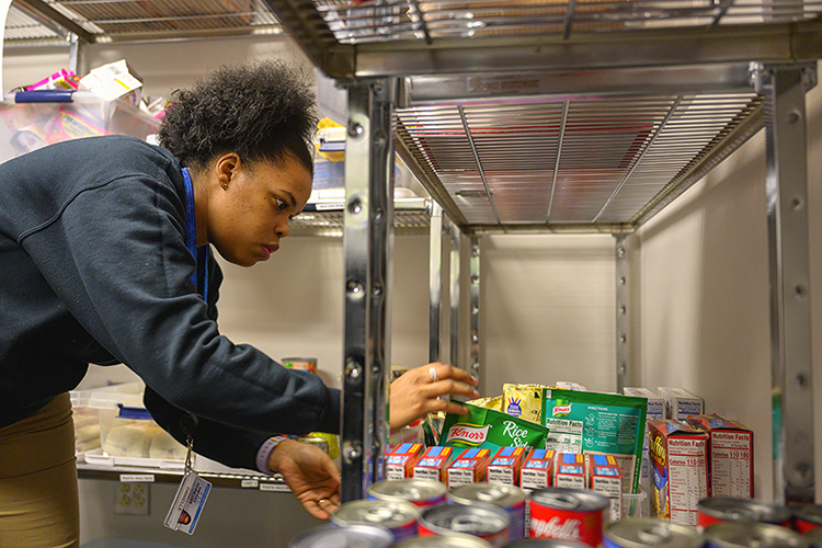 Danielle Rochelle, coordinator of outreach and support programs and supervisor of the MTSU Food Pantry, examines food in the pantry, which will provide food to students from 8 a.m. to 5 p.m. Monday through Friday. (MTSU photo by Cat Curtis Murphy)