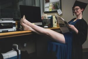 Student Angele Latham sits at her news desk holding a newspaper.
