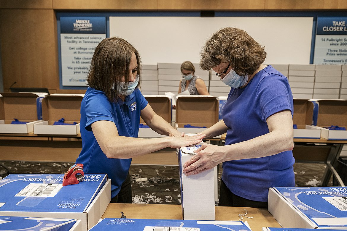From left, Kay Gibbs and Christi Farris, transcript clerks with the MTSU Registar's Office, seal a True Blue Graduation Box for shipping to spring graduates Wednesday, May 20, inside the Student Services and Admissions Center. In the background packing boxes is Registrar Susan Fieldhouse. (MTSU photo by Andy Heidt)
