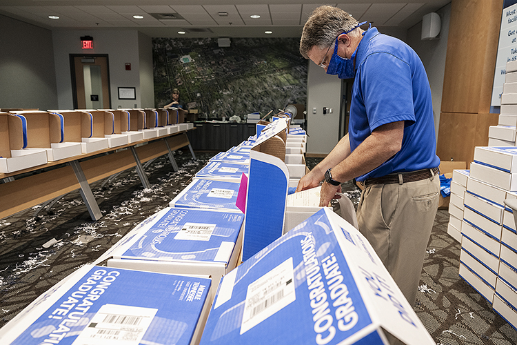 MTSU Provost Mark Byrnes pitches in with packing a True Blue Graduation Box for shipping to spring graduates Wednesday, May 20, inside the Student Services and Admissions Center. (MTSU photo by Andy Heidt)