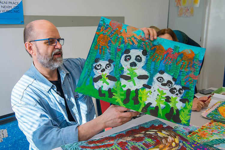 """Visual artist Josef Zednik, chairman of the 48th International Children's Exhibition of Fine Arts Lidice panel of judges, examines one of more than 22,000 entries from 78 countries this spring in the 2020 competition for children ages 4 to 16 at the ICEFA headquarters in Lidice, Czech Republic. Students from the Tennessee School for the Blind in Nashville, guided by MTSU art education students, earned an honorable mention for their one-minute stop-motion animated video entry, """"Arctic Blues."""" (Photo courtesy of ICEFA Lidice)"""