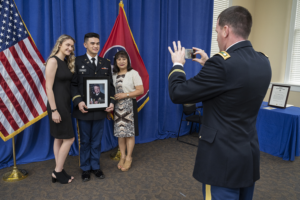 U.S. Army Lt. Col. Carrick McCarthy, right, takes a cell phone photo of newly commissioned 2nd Lt. Curtis Rookard Jr., of Oak Ridge, Tenn., Tuesday, May 12, during the MTSU ROTC commissioning ceremony in the Tom H. Jackson Building's Cantrell Hall. Rookard holds a photo of his father, Lt. Cmdr. Curtis Rookard Sr. Lily Hendrickson, left, Curtis Rookard Jr.'s girlfriend, and his mother, Marita Rookard, attended the ceremony. (MTSU photo by Andy Heidt)