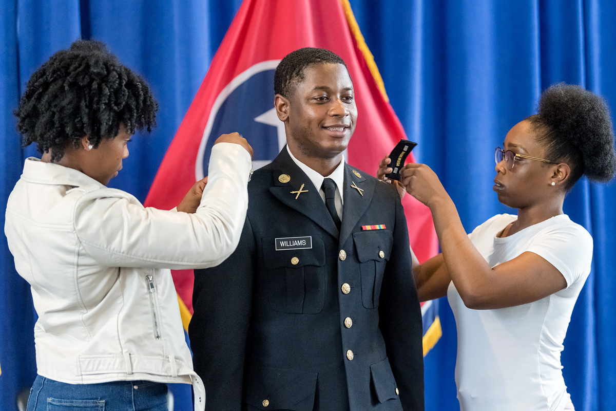 Best friends Terrah Black, left, and Melanie Halmon pin Master of Science in Professional Science biostatistics major Juante J. Williams of Memphis, Tenn., during the ROTC commissioning ceremony in the Tom H. Jackson Building's Cantrell Hall Friday, May 8. (MTSU photo by J. Intintoli)