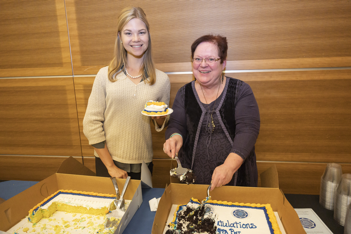 Ella Morin, left, an MTSU Honors College student from Knoxville, Tenn., volunteers with Honors College executive aide Cindy Phiffer in serving cake at the Phi Kappa Phi initiation event in November 2019. Morin is a member of Omicron Delta Kappa. (MTSU photo by Cat Curtis Murphy)