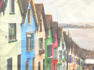 A street in Cobh, Ireland, lined with colorful houses that slope into the sea.