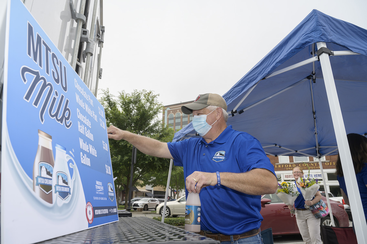 MTSU Farm Laboratories Director Matthew Wade opens the Creamery refrigerated truck's back door to bring more chilled milk out for a customer following a sale Saturday, June 6, at the Main Street Murfreesboro Saturday Market outside the Rutherford County Courthouse. (MTSU photo by Andy Heidt)