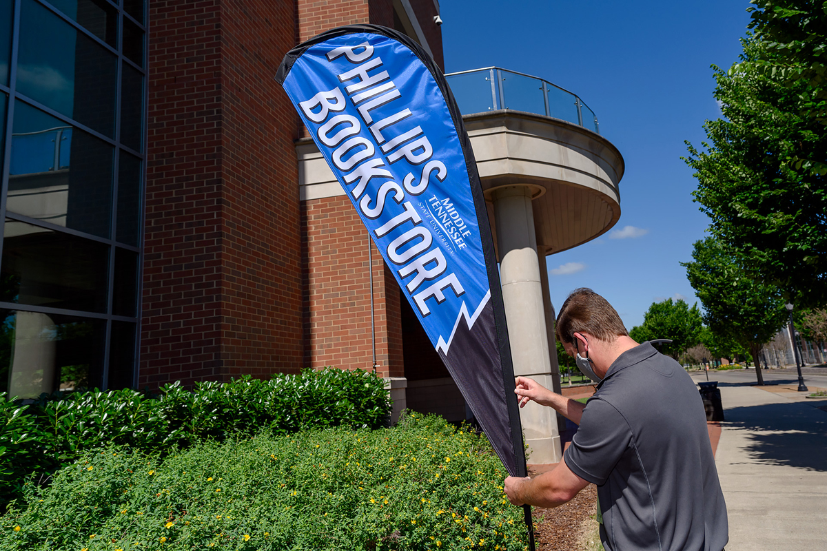 David Phillips, textbook manager at the just-reopened MTSU Phillips Bookstore operated by Barnes & Noble College, adjusts the sign directing foot traffic at the Student Union Building exterior entrance facing MTSU Boulevard Tuesday, June 16. Business hours presently are 10 a.m. to 2 p.m. Monday through Friday. (MTSU photo by J. Intintoli)