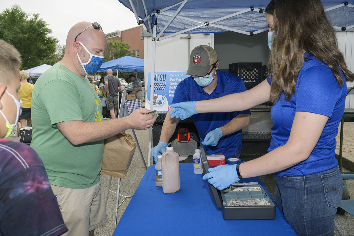 MTSU National Alumni Association Board member Jonathan Harmon of Murfreesboro buys the popular chocolate and whole white milk at the MTSU Creamery vendor spot Saturday, June 6, at the Main Street Murfreesboro Saturday Market outside the Rutherford County Courthouse. (MTSU photo by Andy Heidt)