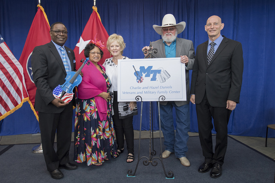 MTSU President Sidney A. McPhee, left, first lady Elizabeth McPhee, Hazel Daniels, Charlie Daniels and Keith M. Huber, senior adviser for veterans and leadership initiatives, display the new Charlie and Hazel Daniels Veterans and Military Family Center logo unveiled in an Aug. 23 celebration. The event recognized the couple and The Journey Home Project for gifts totaling $120,000 for the center. Daniels, who died Monday, July 6, autographed the patriotic fiddle McPhee is holding and presented it to the center as a gift from him and the foundation. (MTSU file photo by Andy Heidt)