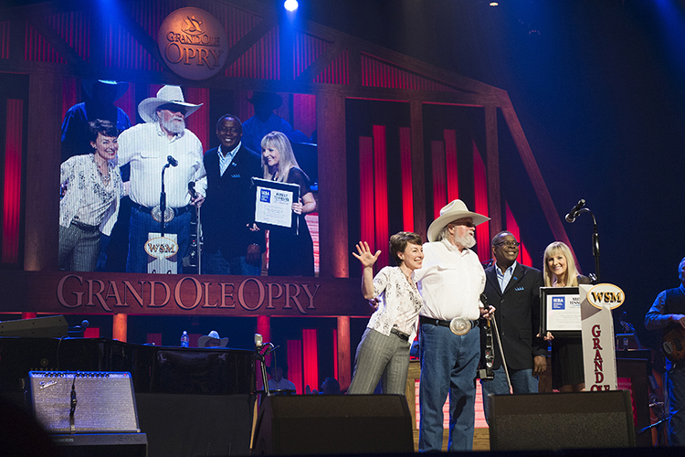 MTSU President Sidney A. McPhee, second from right, presents country music star Charlie Daniels with a framed announcement of the Charlie Daniels Scholarship at MTSU. Joining McPhee and Daniels on stage Saturday night at the Grand Ole Opry is Pam Matthews, left, executive director of the International Entertainment Buyers Association, and MTSU student Jordan Todd, a junior recording industry major, right. Daniels passed away Monday, July 6, at (MTSU file photo by Andy Heidt)